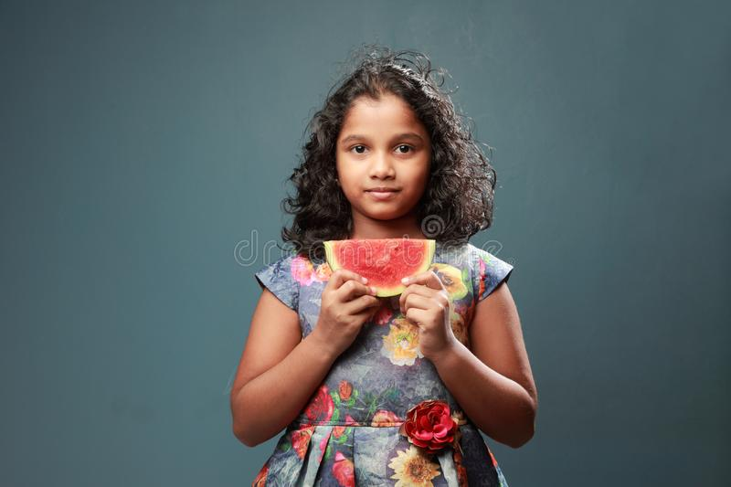 A little girl holds a slice of watermelon. Happy little girl holds a slice of watermelon royalty free stock photo