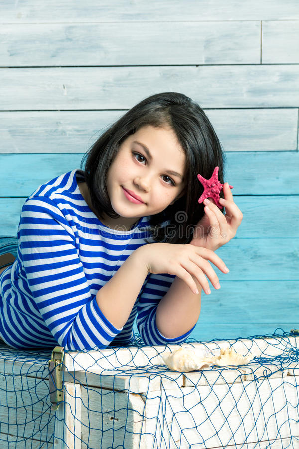 Little girl holds a starfish in hair royalty free stock image