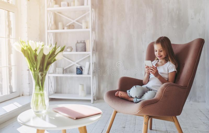 Little girl at home. Cute little girl is sitting in big chair at home with smart phone in hands royalty free stock photography