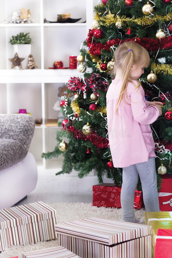 Little girl at home decorating the Christmas tree stock photos