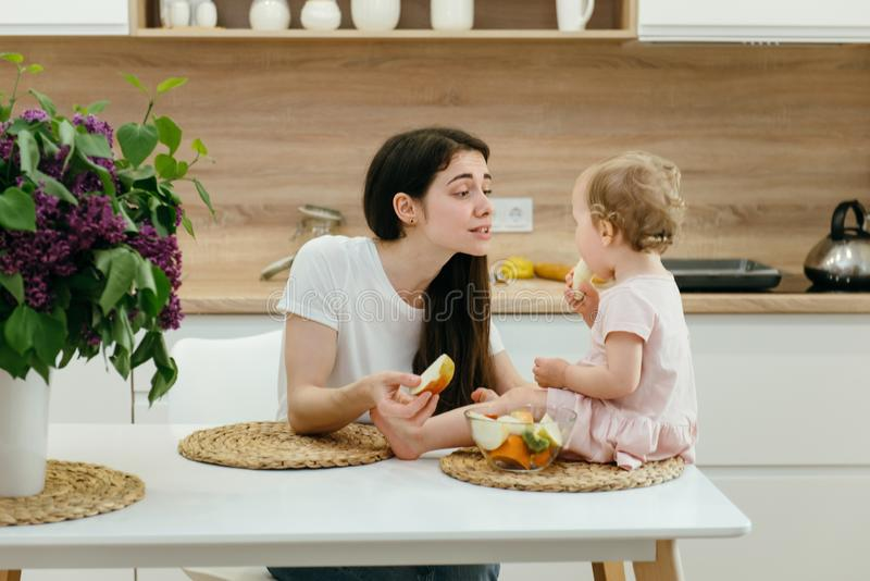 Little girl on the home kitchen having breakfast, fresh fruits. Happy family with little girl on the home kitchen having breakfast, fresh fruits. Toddler with stock photo