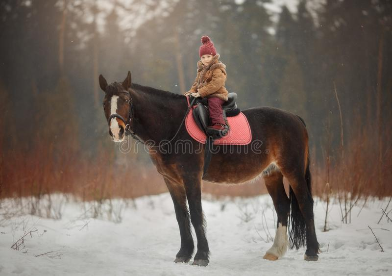 Little girl with horse outdoor portrait at spring day. Little girl with horse outdoor portrait at snowy spring day on brown forest background royalty free stock photography