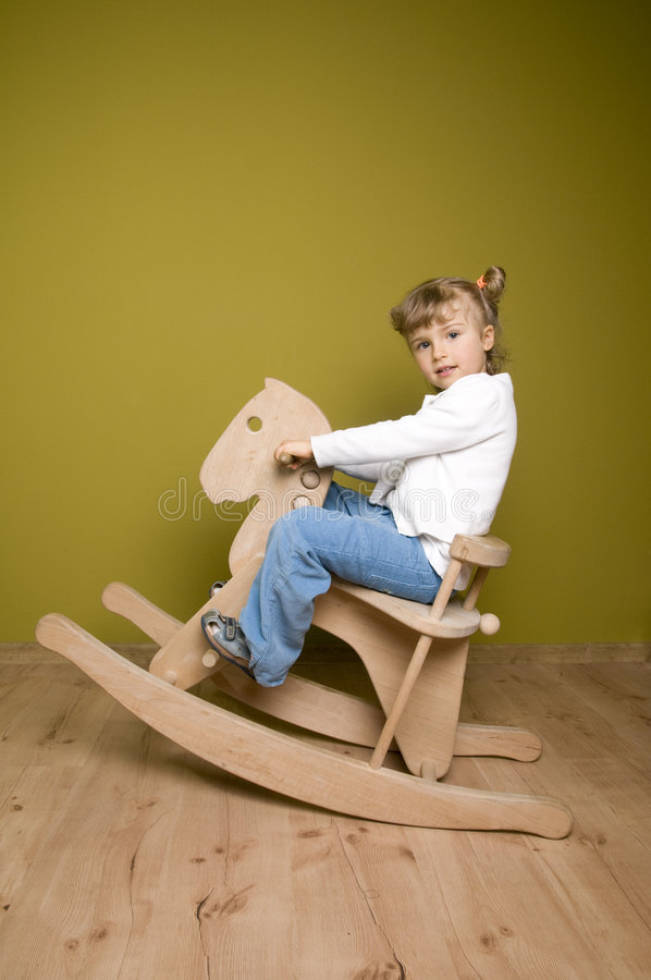 Little girl and horse - rocking chair royalty free stock photos