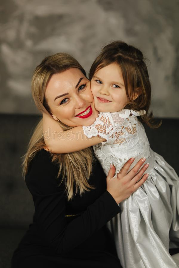 Little girl hug mother and smile. Happy young mom with her daughter at home royalty free stock photography