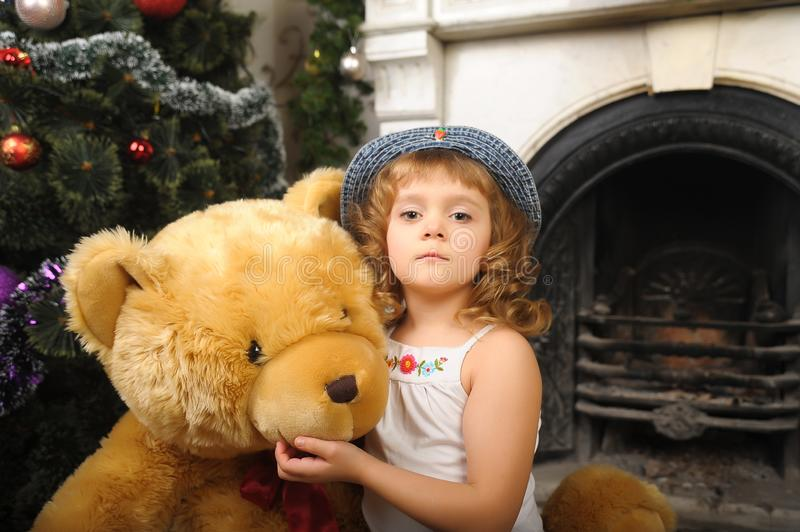 Little girl hugging a big toy bear sitting stock photo