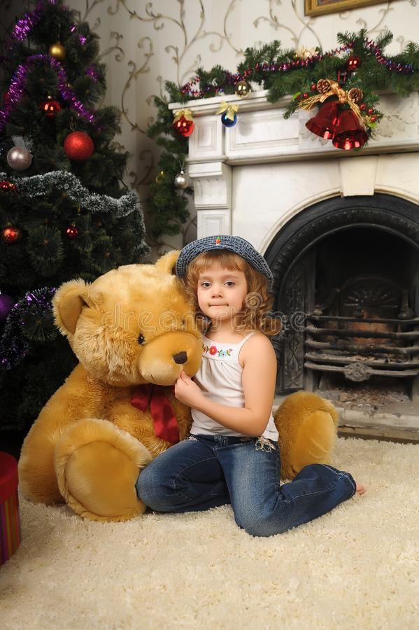 Little girl hugging a big toy bear sitting stock image