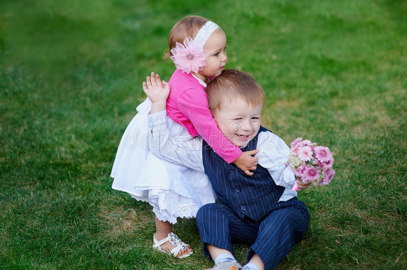 Little girl hugging a boy with a bouquet of flowers in park stock photography