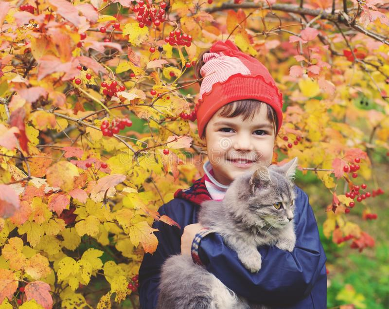 Little girl hugging a cat in the garden royalty free stock images