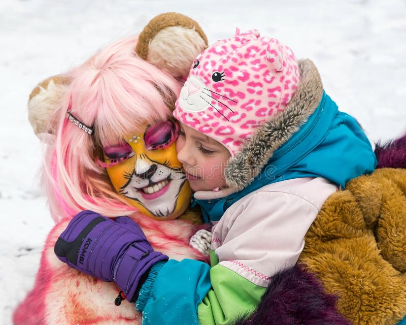 Little girl hugging female clown in animal disguise royalty free stock images