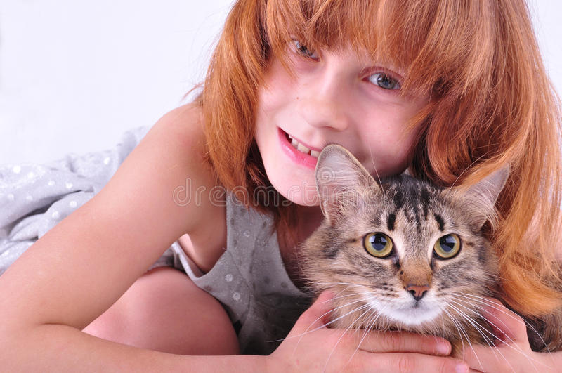 Little girl hugging her cat. Beautiful happy red little girl hugging her cat royalty free stock photos