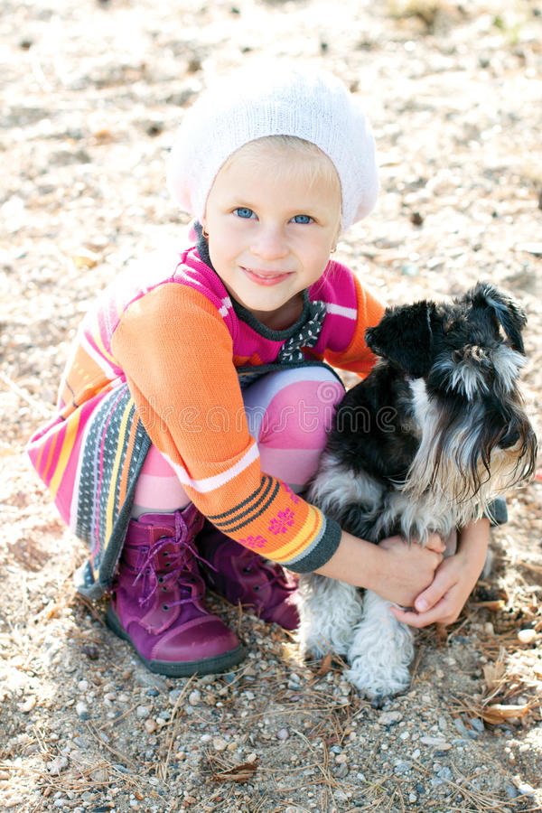 Little girl hugging her dog. Little girl walking with a dog on the street in the summer royalty free stock photography