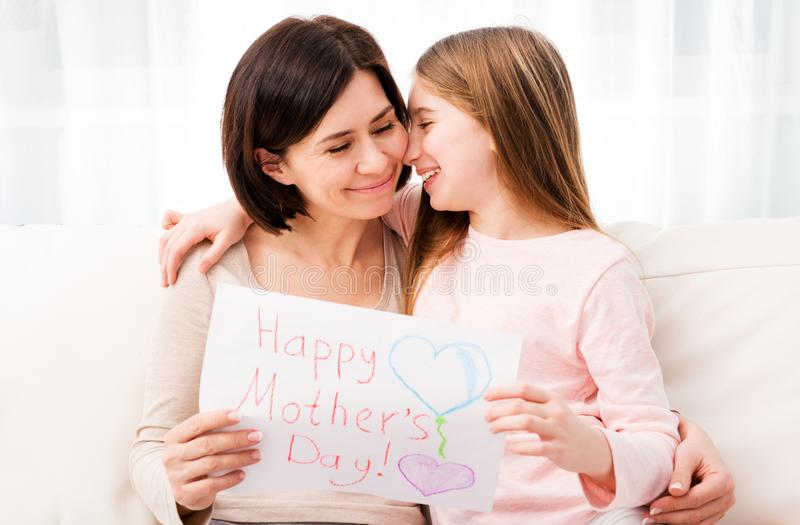 Little girl hugging her mother and holding greating card royalty free stock images