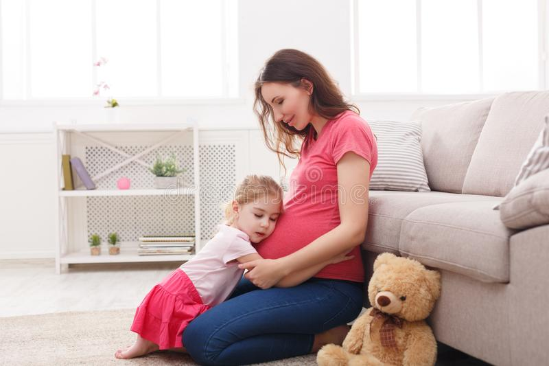 Little girl hugging her pregnant mother belly stock images