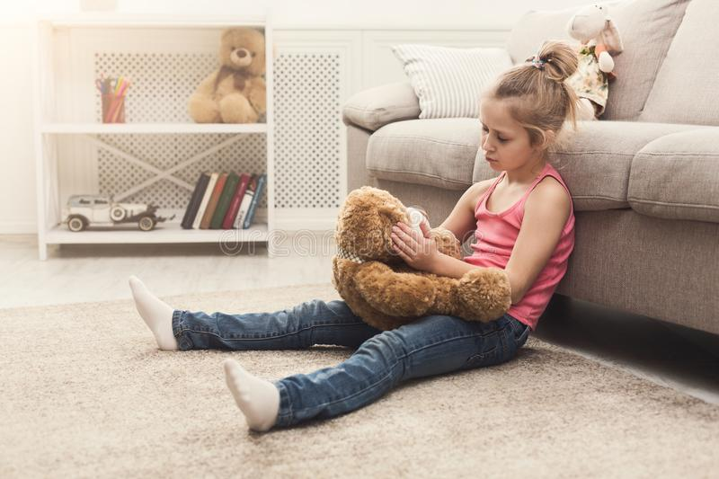 Little girl hugging her teddy bear on floor stock photos