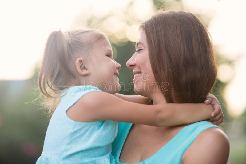 Girl hugging mother outdoors in park royalty free stock image