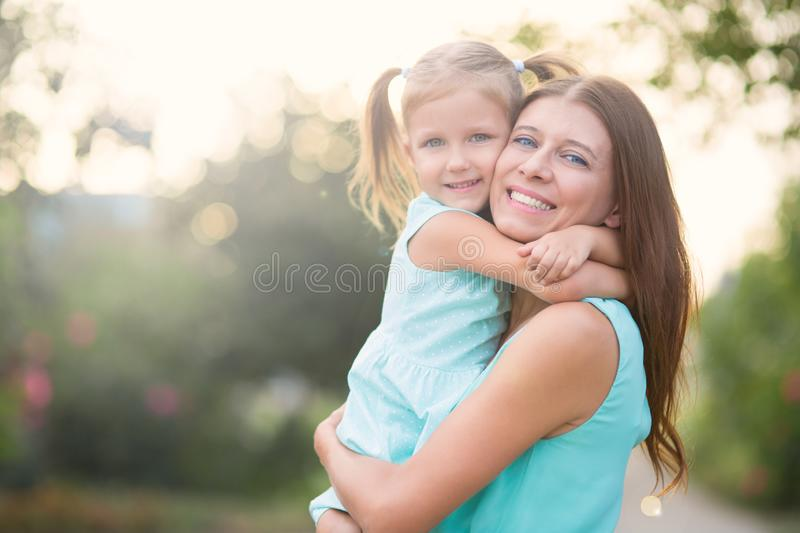 Girl hugging mother outdoors in park stock photo
