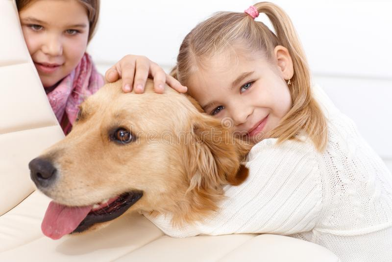 Little girl hugging pet dog smiling stock images