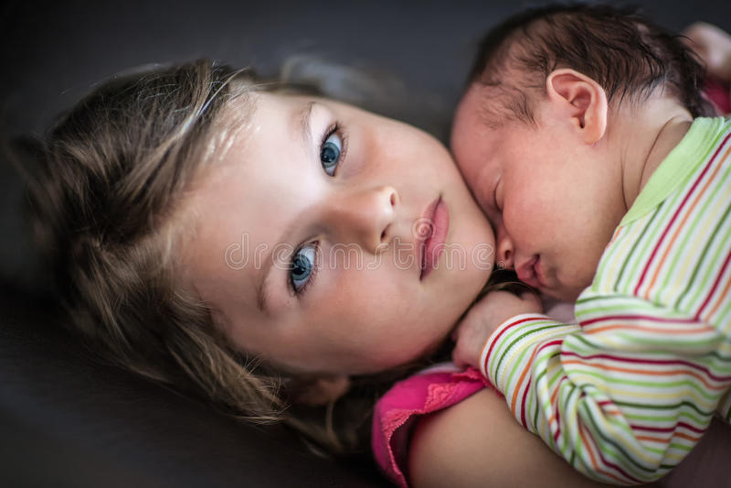 Little girl hugs her newborn sleeping sister foto de archivo
