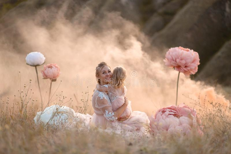 A little girl hugs mom sitting in a field surrounded by unreal big pink decorative flowers stock images