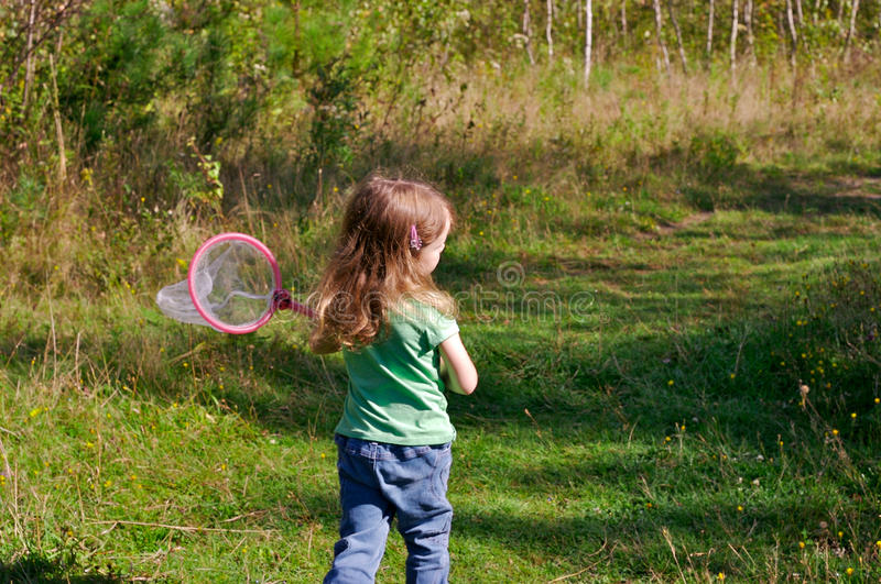 Girl hunting butterflies. Little girl hunting butterflies with a net in a trail in the woods stock photography