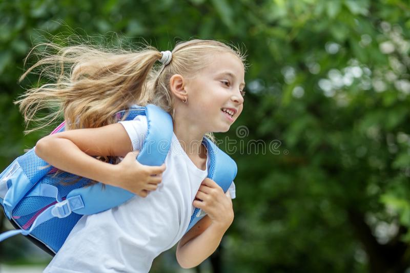 A little girl hurries to school with a backpack. The concept of school, study, education, friendship, childhood. stock photo