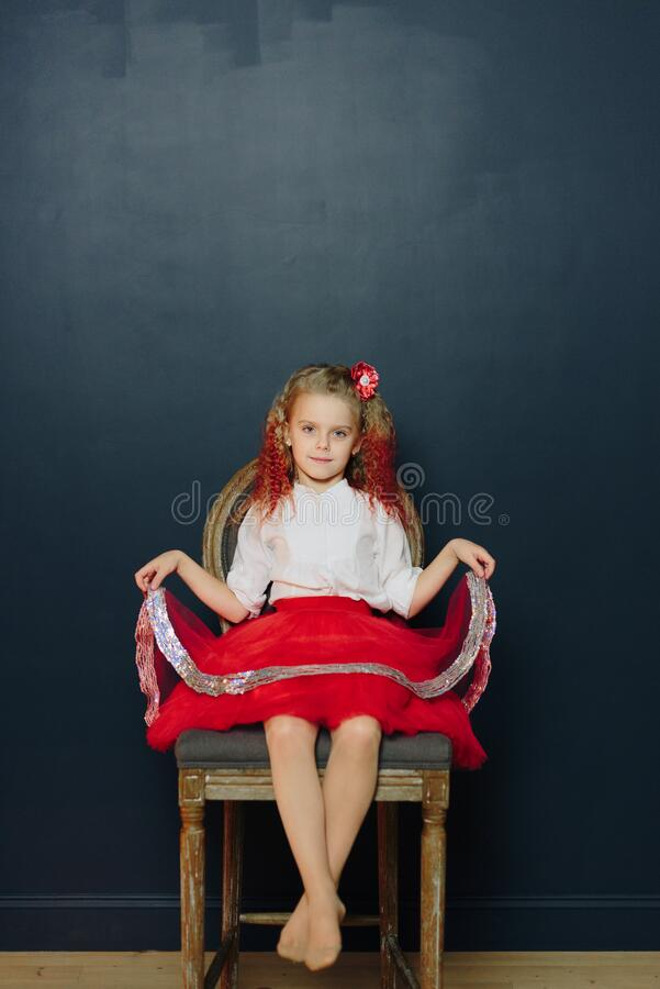 Free Little Girl In Dress Sits On A Chair Against A Dark Background Royalty Free Stock Photos - 169484508