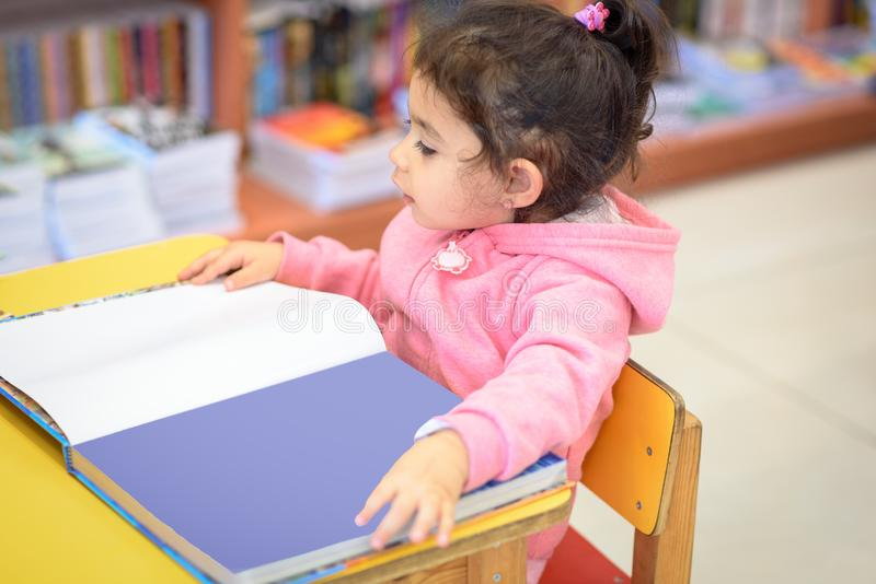 Little Girl Indoors In Front Of Books. Cute Young Toddler Sitting On A Chair Near Table and Reading Book. Library, Shop. stock photos