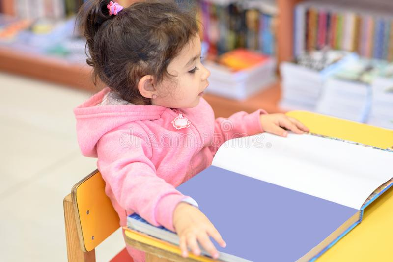 Little Girl Indoors In Front Of Books. Cute Young Toddler Sitting On A Chair Near Table and Reading Book. stock image