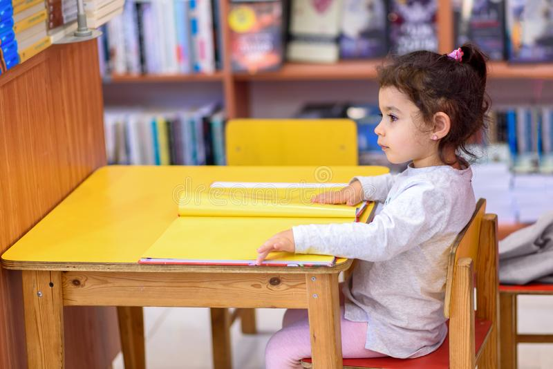 Little Girl Indoors In Front Of Books. Cute Young Toddler Sitting On A Chair Near Table and Reading Book. stock photo