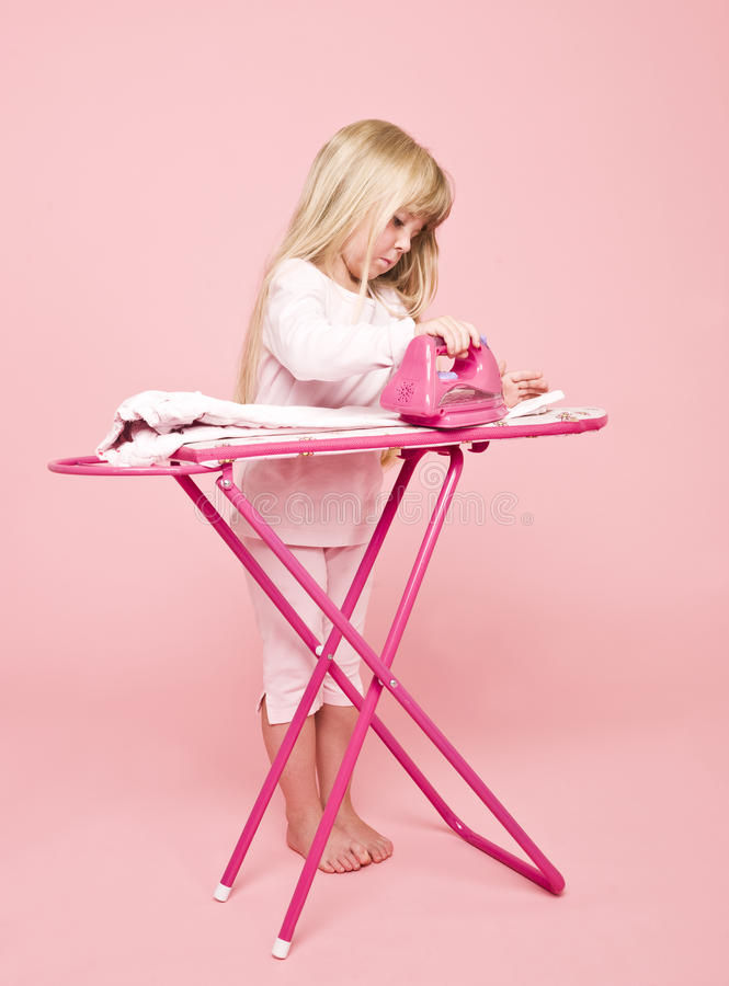Little girl ironing dress stock photo