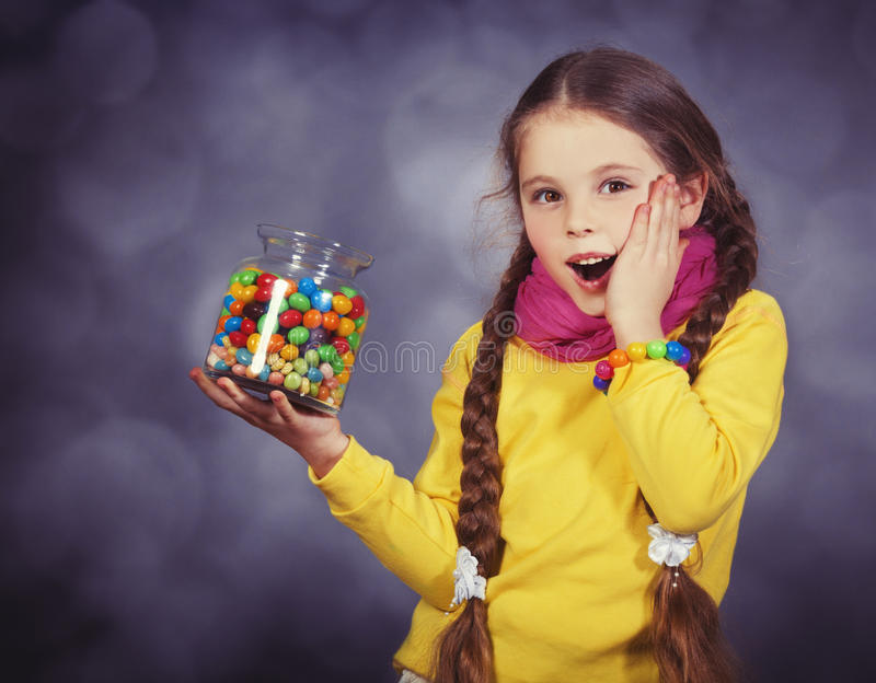 Little girl with jelly bean. Studio shot with a little noise stock photo