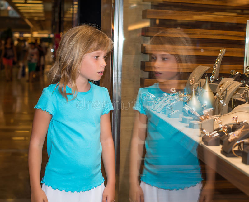 Little girl at jewelry store. Little girl looking at jewelry store royalty free stock photos