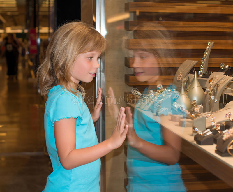 Little girl at jewelry store. Little girl looking at jewelry store royalty free stock photography