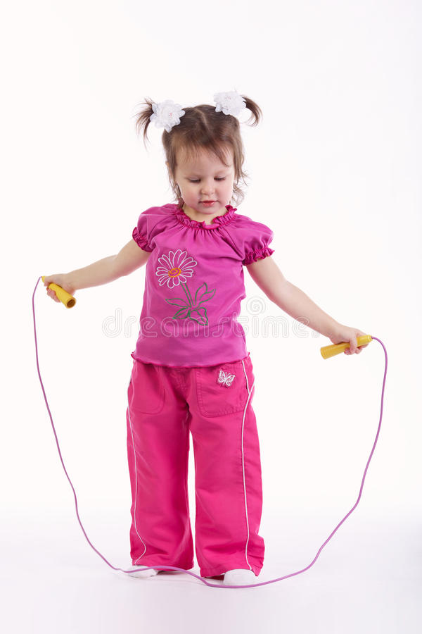 Little girl with jump rope on white. Photo of little girl with jump rope on white stock photography