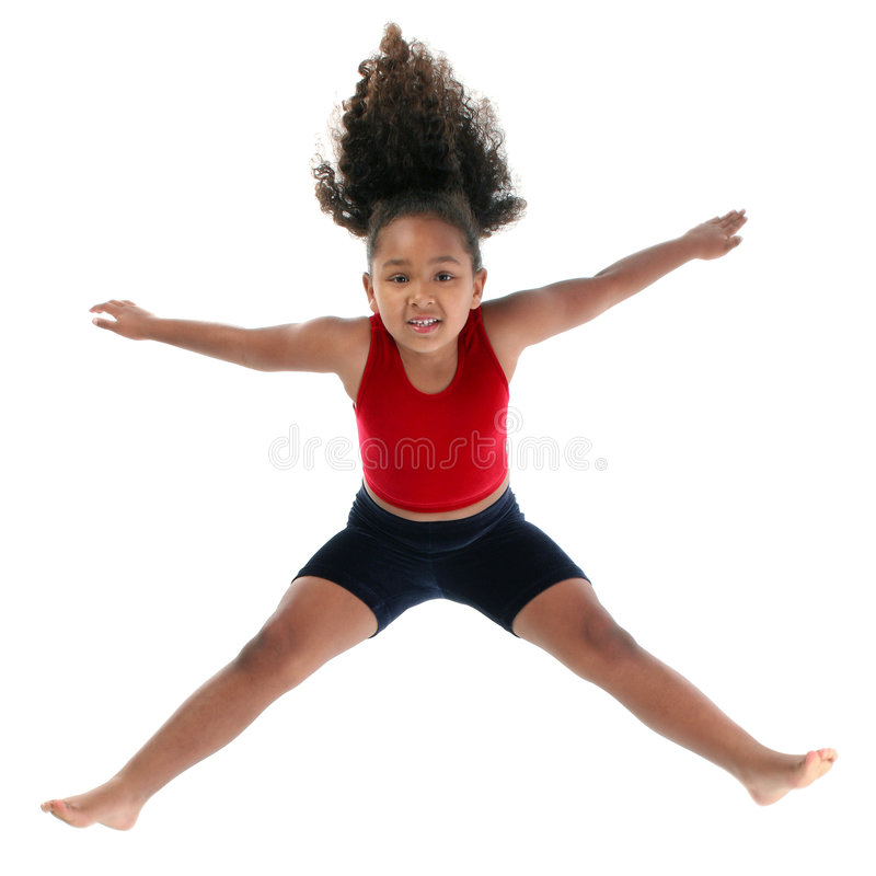 Little girl jumping. Five year old smiling multiracial girl in mid-jump, with her arms and legs extended outward. Isolated on a white background stock images