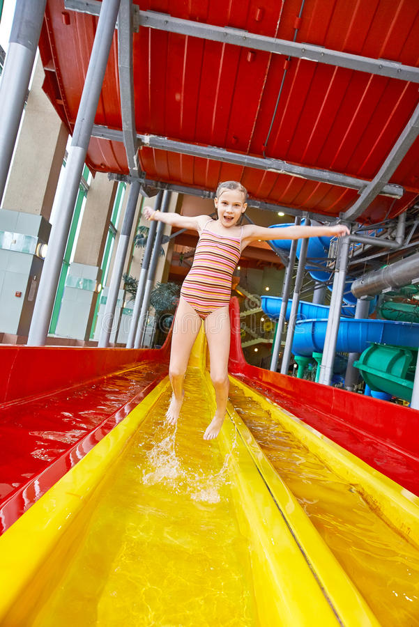 Little girl jumping in aquapark stock images
