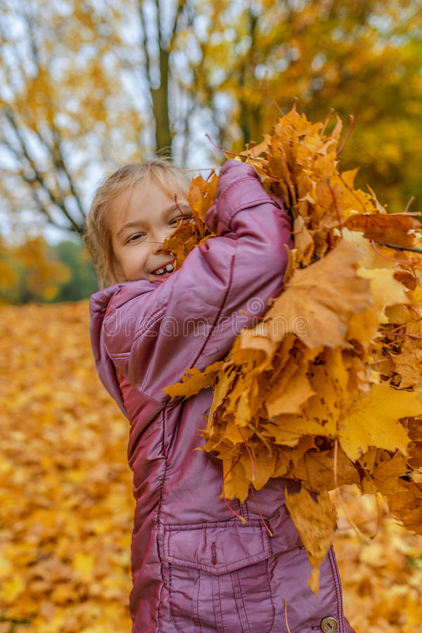 Little girl jumping on background of yellow leaves. Little cheerful beautiful girl jumping on a background of yellow autumn maple leaves stock photos