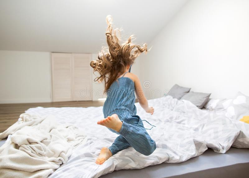 Little girl jumping at home on bed royalty free stock image