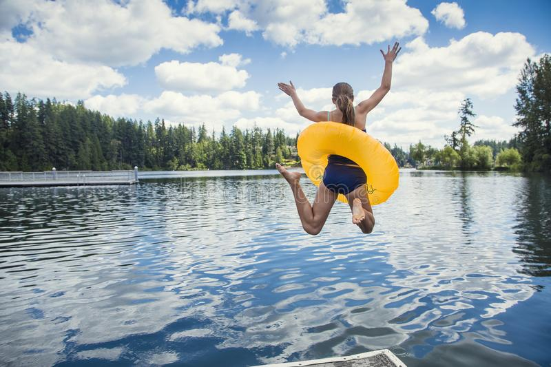 Girl jumping off the dock into a beautiful mountain lake. Having fun on a summer vacation royalty free stock image