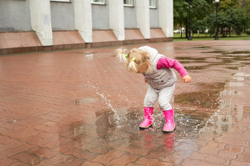 A little girl is jumping in puddles, flying drops of water.  stock photography
