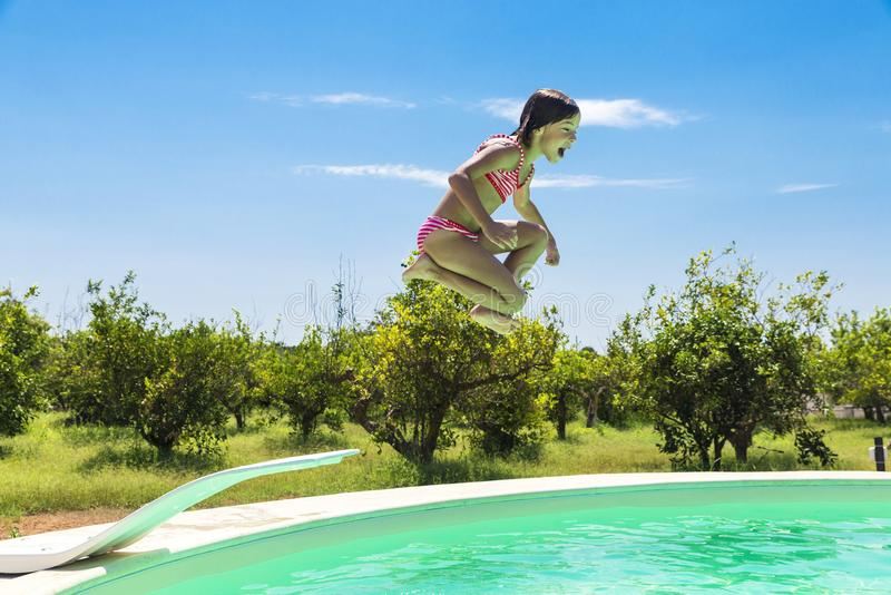 Little girl jumping in pump in an outdoor pool royalty free stock image