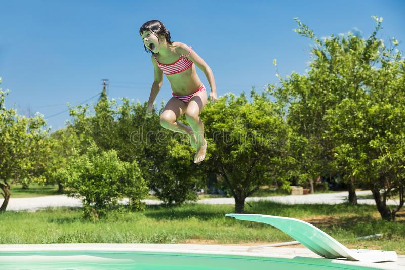 Little girl jumping in pump in an outdoor pool royalty free stock photos