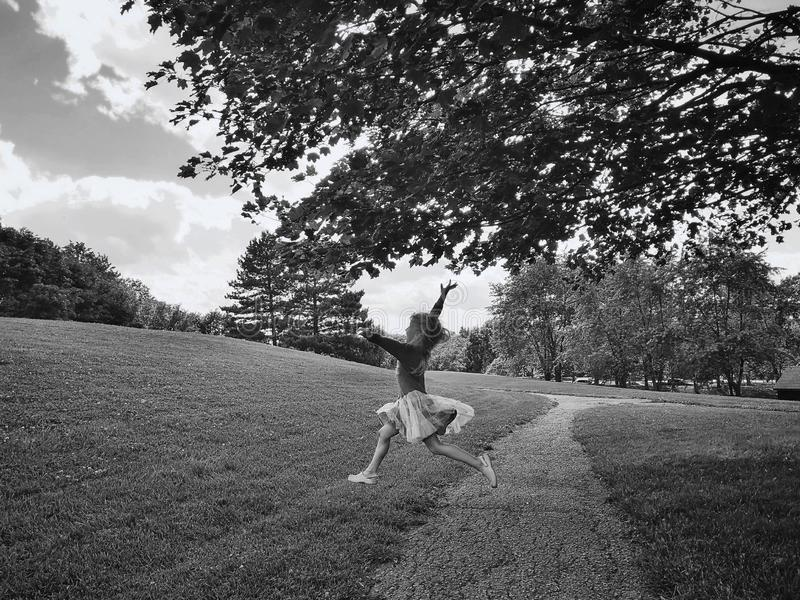 Little girl jumping running in park outside on summer day. Black and white portrait of funny happy smiling child. Funny preschool little girl jumping running in royalty free stock photography