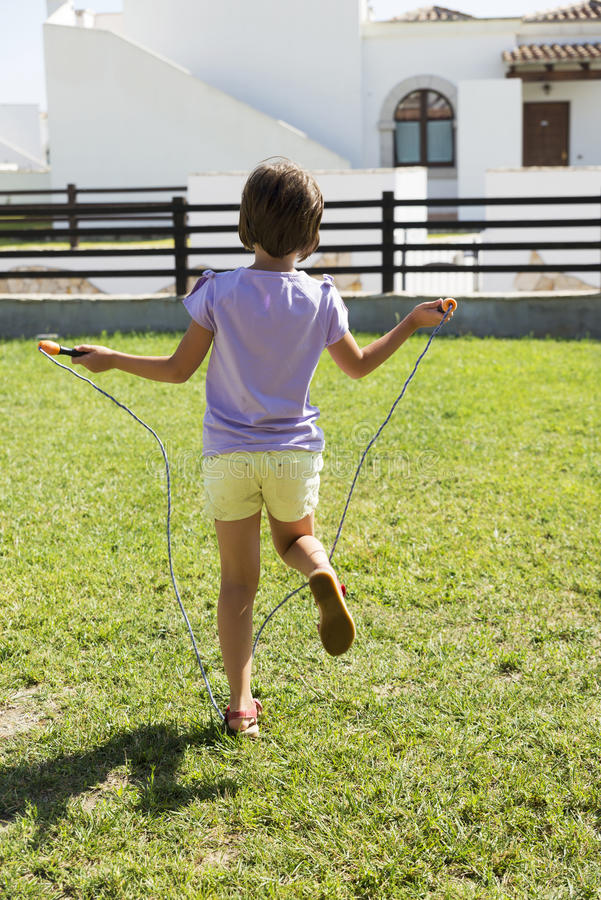 Little girl jumping with skipping rope. Little girl having fun outdoors with a skipping rope royalty free stock images