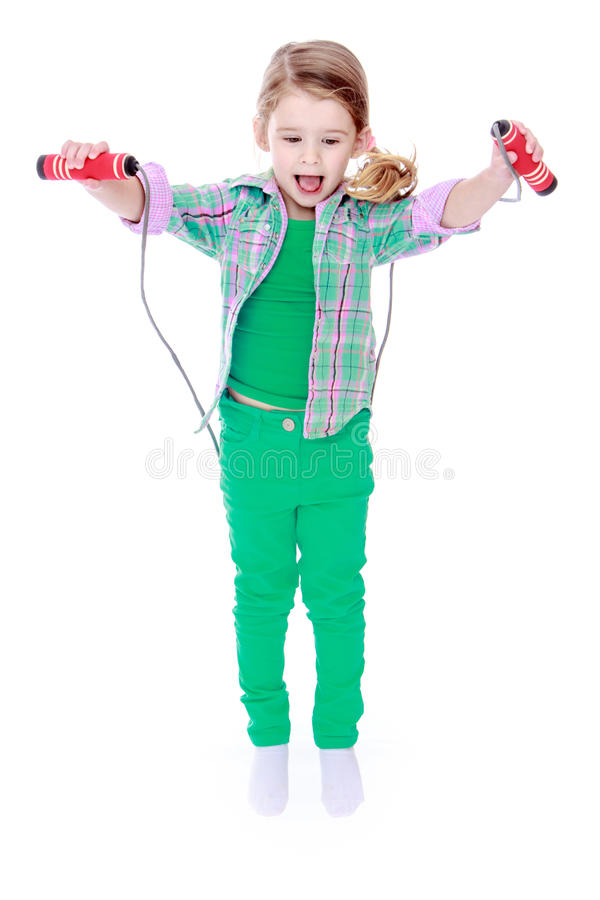 Little girl jumping with the skipping rope royalty free stock photo
