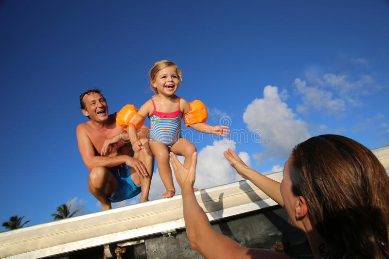 Little girl jumping to the sea. Little girl jumping from pontoon to mother's arms stock photos