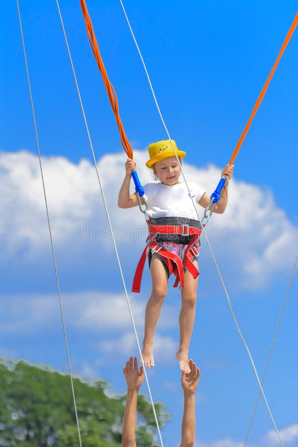 A little girl jumps high on a trampoline with rubber ropes again stock image