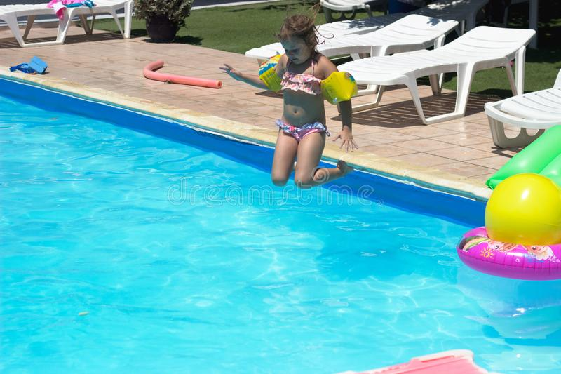 Little girl jumps in the pool; summertime background stock photography