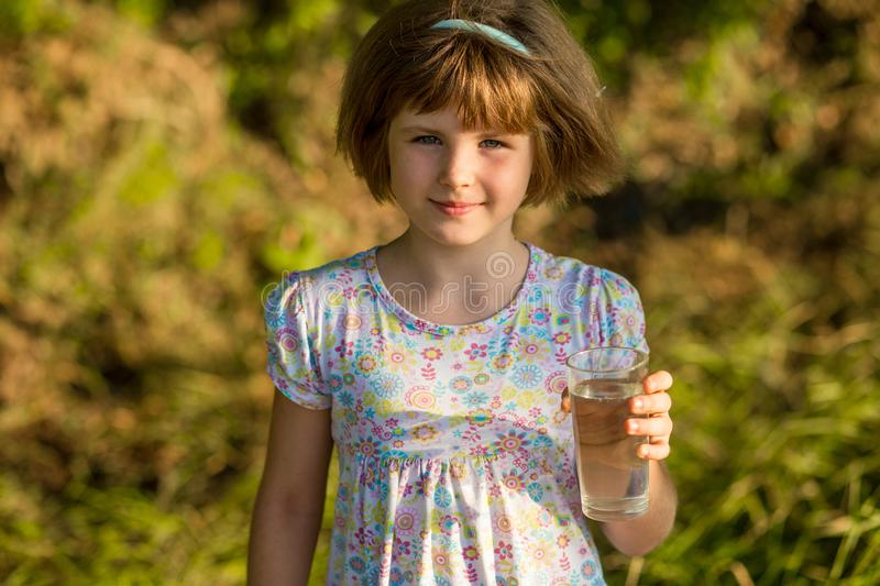 Little girl kid with glass of water in morning, drink every day royalty free stock photo