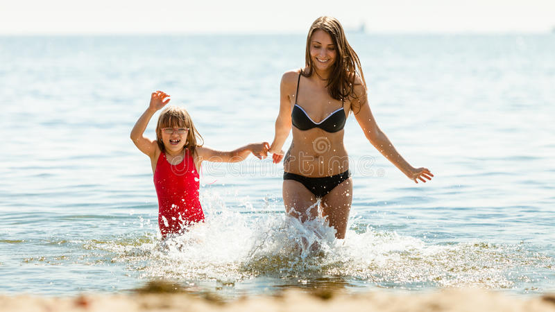 Little girl kid and woman mother in sea water. Fun. Little girl child and mother running having fun in ocean. Kid and women bathing in sea splashing water stock images